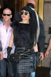 Music icon Lady Gaga proves that more is more. She was spotted in Manhattan in an all-black ensemble. She wore a black feather top and a quilted leather skirt paired with black gloves and a black Chanel quilted bag. To finish off this quirky look, Lady Gaga wore her black and white hair in a side ponytail with straight bangs.