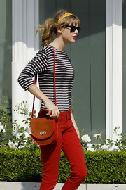 Taylor Swift looked adorable, as always, carrying this leather shoulder bag with red binding.