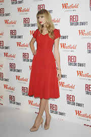 Nude round-toe pumps softened the look of Taylor's cherry-red dress, making the singer look lovelier than ever!