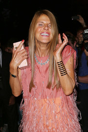 Anna dello Russo accessorized with a simple yet elegant pink box clutch by Saint Laurent during the brand's fashion show.