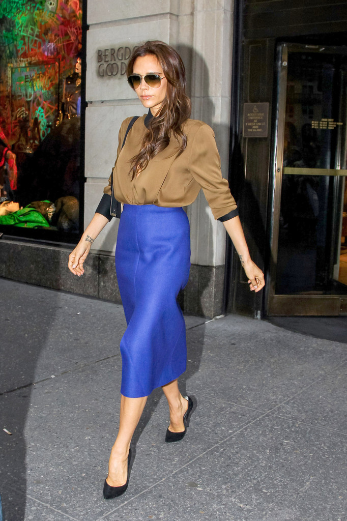 Victoria Beckham, wearing bright purple skirt with plunging cut out blouse seen shopping at Bergdorf Goodman store in New York.