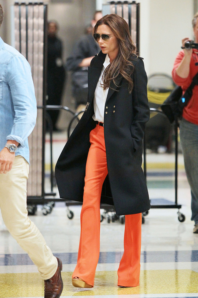Victoria Beckham, wearing striking orange pants with a white top and black overcoat, seen arriving at JFK Airport in New York City.