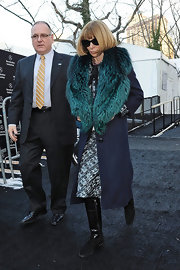 Anna Wintour plays up the glamor with a blue and turquoise fur trimmed coat while attending Diane von Furstenberg's runway show.