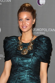 Whitney Port paired her bold teal dress with a bronzed statement necklace.