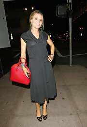 Brooke Mueller added a splash of color to her gray dress with a red textured tote.