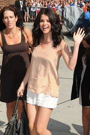 Selena Gomez paired her nude tank with and white shorts with medium curls.