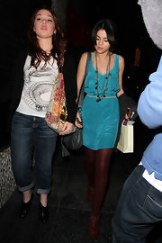 Selena mixes colors with maroon stockings and a turquoise silk dress while out shopping with friends.