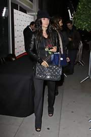 Courteney Cox carried an oversize gray Chanel bag. A black hat completes the actress' hip look.