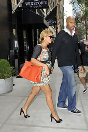 Beyonce added a pop of color to her black and white ensemble with a bright orange leather handbag.