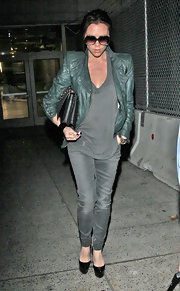 Victoria wears a muted teal leather jacket with her gray ensemble at LAX.