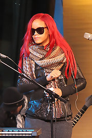 Rihanna wears a couple layers of long knit colorful scarves over her leather jacket.
